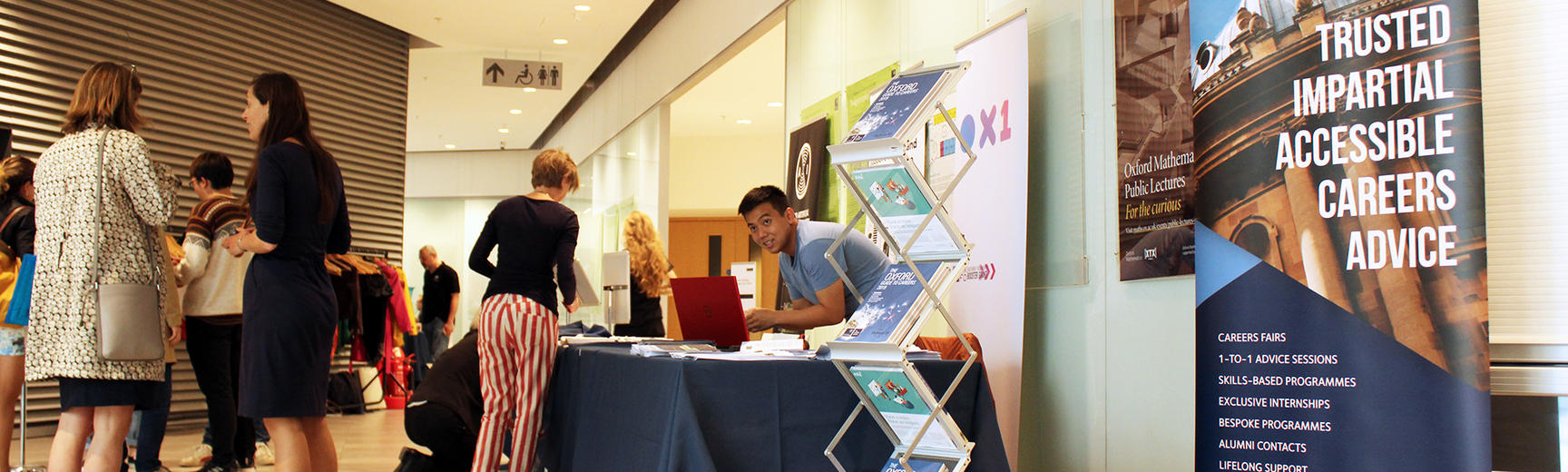 people in front of careers service table at event