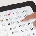 Close up of hand selecting answer on a tablet with multiple choice test