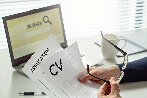 Person holding glasses in one hand with a CV and application in the other hand in front of a laptop monitor that says 'job search'