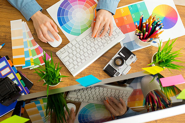 Overhead perspective of person using a computer with colour cards on the desk