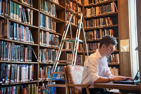 Person at library using a laptop in front of ladder and bookshelves