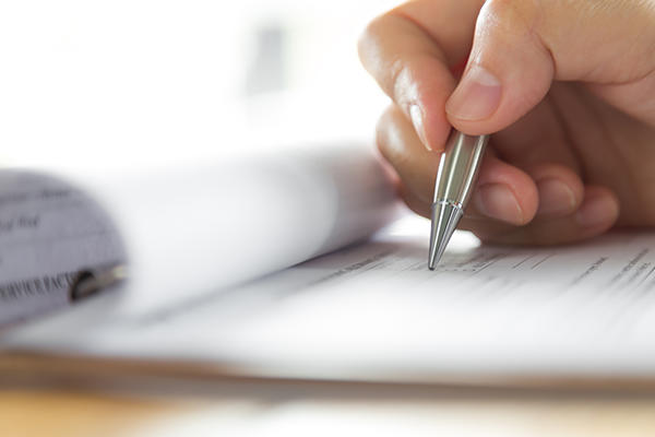 Close up of hand holding pen to a paper form