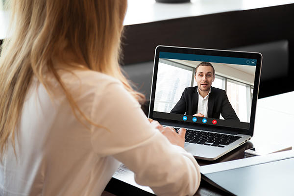 Over-shoulder view of woman on a video call with a man